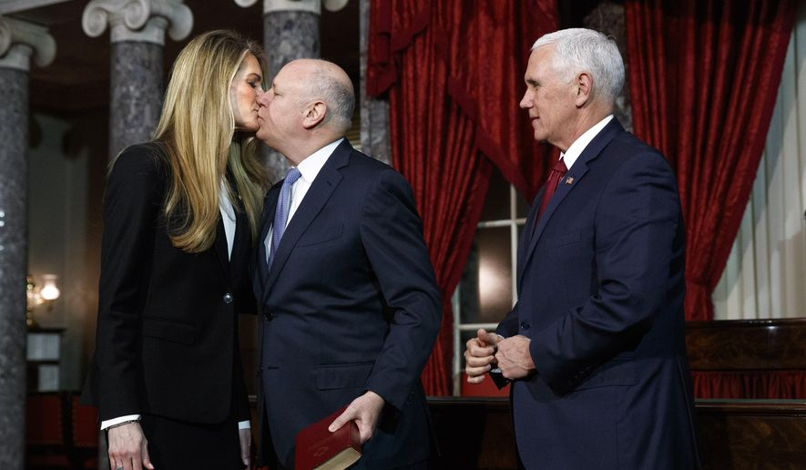Sen. Kelly Loeffler, R-Ga., left, gets a kiss from her husband Jeffrey Sprecher, after Vice President Mike Pence presided in a re-enactment of Loeffler's swearing-in Monday Jan. 6, 2020, in the Old Senate Chamber on Capitol Hill in Washington. (AP Photo/Jacquelyn Martin)