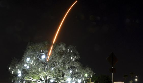 In a time exposure, the SpaceX Falcon 9 rocket launches from Cape Canaveral, as seen from Viera, Fla., late Monday, Jan. 6, 2020. In the foreground is the traffic roundabout, which is lit up for the holiday season. (Tim Shortt/Florida Today via AP)