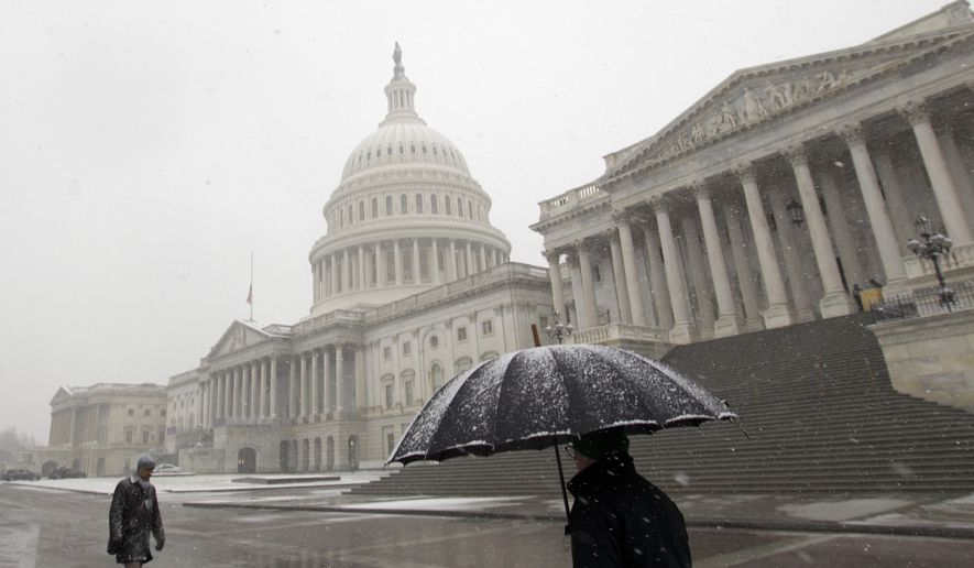 Pedestrians walk under a snowfall outside of U.S. Capitol building, Wednesday, March 21, 2018, in Washington. (AP Photo/Jose Luis Magana) **FILE**