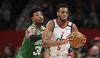 Washington Wizards guard Troy Brown Jr. (6) handles the ball in front of Boston Celtics guard Marcus Smart (36) during the second half of an NBA basketball game, Monday, Jan. 6, 2020, in Washington. The Wizards won 99-94. (AP Photo/Nick Wass)