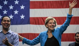 Democratic presidential candidate Sen. Elizabeth Warren, D-Mass., right, joined by former Secretary of Housing and Urban Development and presidential candidate Julian Castro, left, wave to supporters after speaking at a campaign rally, Tuesday, Jan. 7, 2020, at Brooklyn's King Theatre in New York. (AP Photo/Bebeto Matthews)