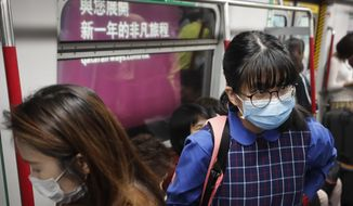 Commuters wear protection masks inside a subway train in Hong Kong, Tuesday, Jan. 7, 2020. Hong Kong health chief Sophia Chan said Tuesday that a respiratory illness whose cause remains unknown will be added to an official list of diseases that medical practitioners are required to report to the government. (AP Photo/Andy Wong)