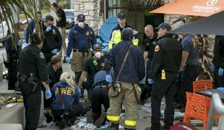 Paramedics perform CPR on a stabbing victim in Austin, Texas on Friday, Jan. 3, 2020. (Jay Janner/Austin American-Statesman via AP)