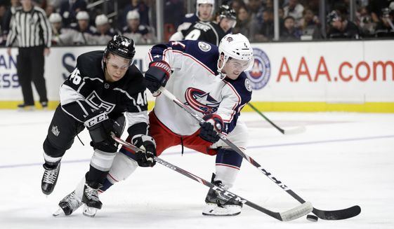 Columbus Blue Jackets' Scott Harrington, right, is defended by Los Angeles Kings' Blake Lizotte during the third period of an NHL hockey game Monday, Jan. 6, 2020, in Los Angeles. (AP Photo/Marcio Jose Sanchez)