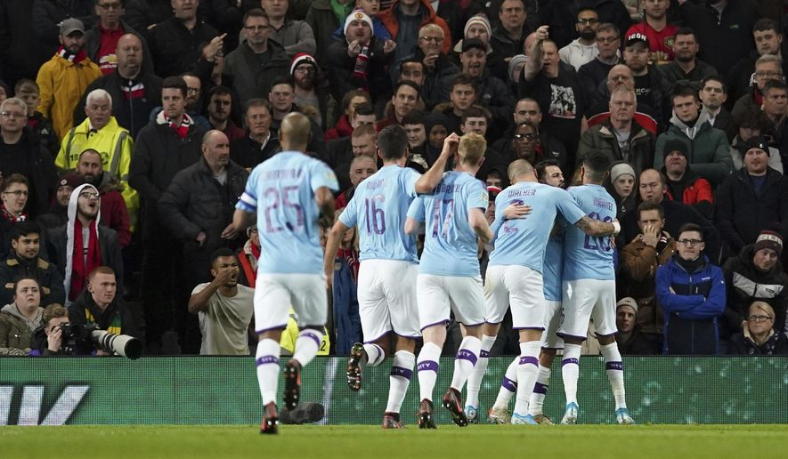 Manchester City's Bernardo Silva, right, is mobbed by his teammates after scoring the opening goal of the game during the English League Cup semifinal first leg soccer match between Manchester United and Manchester City and at Old Trafford, Manchester, England, Tuesday, Jan. 7, 2020. (AP Photo/Jon Super)