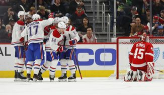 Montreal Canadiens center Nick Suzuki (14) celebrates his goal against Detroit Red Wings goaltender Jonathan Bernier (45) with teammates in the second period of an NHL hockey game Tuesday, Jan. 7, 2020, in Detroit. (AP Photo/Paul Sancya)