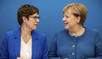 Annegret Kramp-Karrenbauer, left, CDU Federal Chairman and Defence Minister, stands next to Chancellor Angela Merkel (CDU) at the beginning of the meeting of the CDU Federal Executive Committee in the Konrad-Adenauer-Haus in Berlin, German, Monday, Dec. 9, 2019.  (Michael Kappeler/dpa via AP)