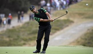 FILE - In this Sunday, Dec. 15, 2019 file photo, International team player Abraham Ancer of Mexico plays his second shot on the 6th hole in his singles match during the President's Cup golf tournament at Royal Melbourne Golf Club in Melbourne. Ancer says he has started a tequila company called Flecha Azuel. (AP Photo/Andy Brownbill, File)