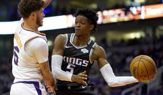 Sacramento Kings guard De'Aaron Fox (5) looks to pass around Phoenix Suns guard Tyler Johnson in the first half during an NBA basketball game, Tuesday, Jan. 7, 2020, in Phoenix. (AP Photo/Rick Scuteri)
