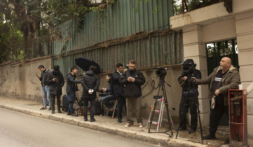 Journalists stand outside of the house of ex-Nissan chief Carlos Ghosn in Beirut, Lebanon, Tuesday, Jan. 7, 2020. Tokyo prosecutors obtained an arrest warrant Tuesday for the wife of Nissan's former chairman, Ghosn, on suspicion of perjury, adding to the couple's legal troubles in the country where he once was revered as a star executive. (AP Photo/Maya Alleruzzo)