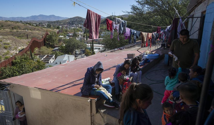 """FILE - In this Oct. 31, 2019 photo, migrants rest at """"La Roca,"""" or The Rock shelter in Nogales, Sonora state, Mexico, near the border fence, top left, that separates Mexico from the U.S. As the U.S. moved aggressively over the past year to sharply reduce the number of asylum seekers arriving at its southwest border, Mexicans were spared, but now Mexico is expressing its displeasure at U.S. plans to send Mexican asylum seekers some 2,000 miles south to Guatemala. (AP Photo/Moises Castillo, File)"""