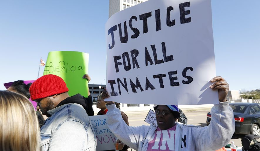 Prisoner advocates hold signs supporting inmate rights at a protest outside the Capitol in Jackson, Miss., Tuesday, Jan. 7, 2020. The protesters called on the federal government to investigate Mississippi's prison system for possible civil rights violations. They say five deaths in recent days highlights deliberate violations of inmates' constitutional rights. (AP Photo/Rogelio V. Solis)