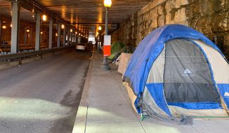 D.C. government workers cleared out all the tents on the sidewalk under the K Street Northeast underpass last week to make room for pedestrians. Many of those homeless folk moved to the L Street Northeast underpass. (Sophie Kaplan/The Washington Times)