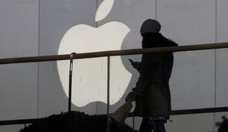 In this Dec. 23, 2013, file photo, a woman using a phone walks past Apple's logo near its retail outlet in Beijing. (AP Photo/Ng Han Guan, File)