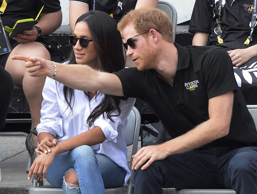 In this Monday, Sept. 25, 2017 file photo Prince Harry and his then-girlfriend Meghan Markle attend a wheelchair tennis event at the Invictus Games in Toronto.  (Nathan Denette/The Canadian Press via AP, FILE) **FILE**