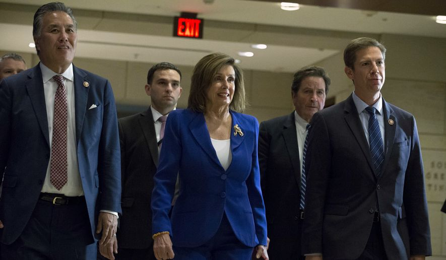 Speaker of the House Nancy Pelosi, D-Calif., accompanied by members of the Congress, arrives for a briefing on last week's targeted killing of Iran's senior military commander Gen. Qassem Soleimani on Capitol Hill, in Washington, Wednesday, Jan. 8, 2020. (AP Photo/Jose Luis Magana)
