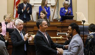 Virginia Gov. Ralph Northam, center, shakes the hand of Del. Suhas Subramanyam, D-Loudoun, while leaving the chamber after delivering his State of the Commonwealth address before a joint session of the Assembly at the state Capitol in Richmond, Va., Wednesday, Jan. 8, 2020. (AP Photo/Steve Helber)