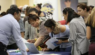In this Sept. 18, 2019, file photo job applicants look at jobs available at Florida International University during a job fair in Miami. On Wednesday, Jan. 8, 2020, payroll processor ADP reported on how many jobs its survey estimates U.S. companies added in December. (AP Photo/Lynne Sladky, File)