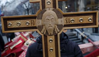 A man holds a cross during a rally in central Belgrade, Serbia, Wednesday, Jan. 8, 2020. Thousands of Serbs have answered a call by the Serbian Orthodox Church to stage a protest against alleged suppression of religious and other rights of minority Serbs in neighboring countries. (AP Photo/Darko Vojinovic)
