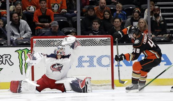 Columbus Blue Jackets goaltender Elvis Merzlikins, left, stops a shot next to Anaheim Ducks' Isac Lundestrom (48) during the first period of an NHL hockey game Tuesday, Jan. 7, 2020, in Anaheim, Calif. (AP Photo/Marcio Jose Sanchez)