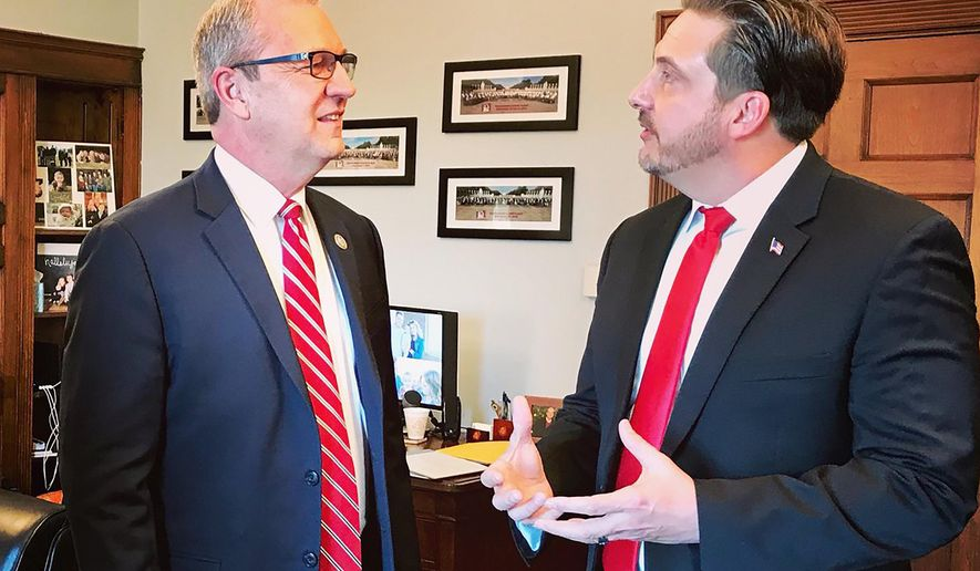FILE - In this Jan. 30, 2019 photo provided by Sen. Kevin Cramer's office, Tommy Fisher, right, talks with Sen. Kevin Cramer, R-N.D., at the lawmaker's office in Washington, D.C. For Fisher, a supporter of President Donald Trump, a federal court hearing set for Thursday, Jan. 9, 2020, next to the U.S.-Mexico border could result in his company getting a chance to prove it can build the president's signature border wall faster and better than the government. (Sen. Kevin Cramer's office via AP, File)