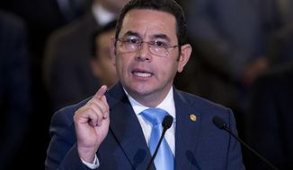File - In this Jan. 7, 2019 file photo, Guatemala's President Jimmy Morales gives a statement, at the National Palace in Guatemala City. Outgoing President Morales says his government has not agreed to receive Mexicans who had sought asylum in the United States. Morales, whose presidency ends next week, said that he had told U.S. officials that would have to be negotiated with his successor. (AP Photo/Moises Castillo, File)