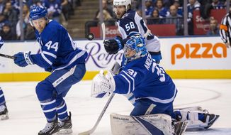 Toronto Maple Leafs goaltender Frederick Andersen (31) makes a save as defenseman Morgan Rielly (44) and Winnipeg Jets center Jansen Harkins (58) look on during the first period of an NHL hockey game, Wednesday, Jan. 8, 2020 in Toronto.(Frank Gunn/The Canadian Press via AP)