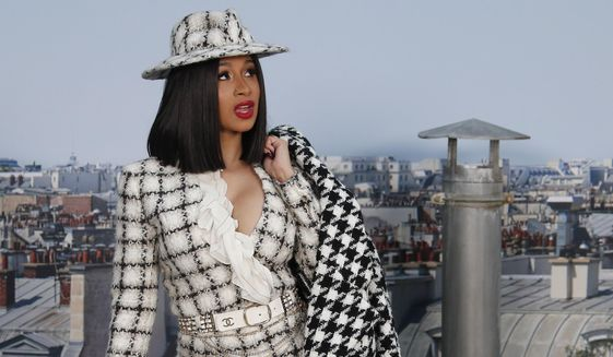 File - In this Tuesday, Oct. 1, 2019 file photo, Singer Cardi B poses for photographers as she arrives for the Chanel Ready To Wear Spring-Summer 2020 collection in Paris, France. Cardi B's announcement in a tweet on Friday, Jan. 3, 2020 that she wants to seek Nigerian citizenship has set off a Twitter feud between her West African fans in friendly rivals Nigeria and Ghana. (AP Photo/Francois Mori, file)