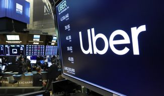"""FILE - In this May 30, 2019, file photo, the logo for Uber appears above a trading post on the floor of the New York Stock Exchange. Ride-hailing giant Uber, along with delivery company Postmates, sued California over a new law that aims to reclassify their drivers and delivery workers as employees instead of contractors. The law, which went into effect last week, could upend the business models of the companies that shaped the so-called """"gig economy,"""" where contract workers use smartphone apps to accept odd jobs driving or delivering goods as frequently as they wish. (AP Photo/Richard Drew, File)"""