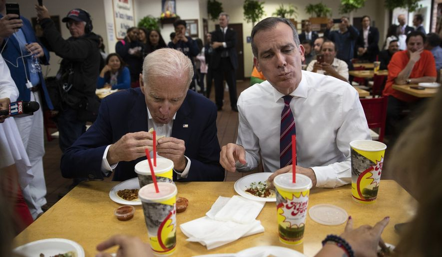 Former vice president and Democratic presidential candidate Joe Biden, left, and Los Angeles Mayor Eric Garcetti eat their tacos at King Taco Wednesday, May 8, 2019, in Los Angeles. (AP Photo/Jae C. Hong)