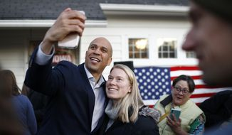 Democratic presidential candidate Sen. Cory Booker, D-N.J., poses for a selfie with an attendee after speaking at a campaign event at the home of Polk County Democratic Chair Sean Bagniewski, Tuesday, Jan. 7, 2020, in Des Moines, Iowa. Booker said a looming impeachment trial and other pressing issues in Washington could deal a big, big blow to his Democratic presidential campaign by keeping him away from Iowa in the final weeks before the Feb. 3 caucuses. (AP Photo/Patrick Semansky)