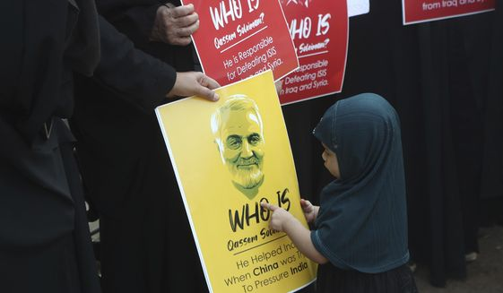 An Indian Shiite Muslim girl points at a portrait of Iranian Gen. Qassem Soleimani who was killed in a U.S. attack, during a protest against the U.S. in Mumbai, India, Thursday, Jan. 9, 2020. (AP Photo/Rafiq Maqbool)