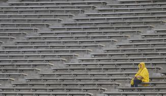 A fan watches Boston College play Cincinnati in the rain during the first half of the Birmingham Bowl NCAA college football game Thursday, Jan. 2, 2020, in Birmingham, Ala. (Photo/Butch Dill)