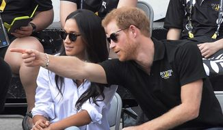 "Prince Harry and his then-girlfriend Meghan Markle attend a wheelchair tennis event at the Invictus Games in Toronto, Monday, Sept. 25, 2017. In a stunning declaration, Britain's Prince Harry and his wife, Meghan, said they are planning ""to step back"" as senior members of the royal family and ""work to become financially independent."" A statement issued by the couple Wednesday, Jan. 8, 2020 also said they intend to ""balance"" their time between the U.K. and North America. (Nathan Denette/The Canadian Press via AP) ** FILE **"