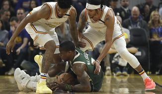 Milwaukee Bucks' Eric Bledsoe, center, keeps the ball from Golden State Warriors' Jacob Evans left, and Damion Lee, right, during the first half of an NBA basketball game Wednesday, Jan. 8, 2020, in San Francisco. (AP Photo/Ben Margot)