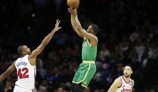 Boston Celtics' Kemba Walker (8) goes up to shoot against Philadelphia 76ers' Al Horford (42) as 76ers' Ben Simmons (25) looks on during the first half of an NBA basketball game, Thursday, Jan. 9, 2020, in Philadelphia. (AP Photo/Matt Slocum)