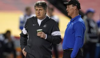 Washington State coach Mike Leach, left, and Air Force  coach Troy Calhoun talk before the Cheez-It Bowl NCAA college football bowl game, Friday, Dec. 27, 2019, in Phoenix. (AP Photo/Rick Scuteri) ** FILE **