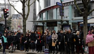 People queue as they wait for a bus in Paris, Tuesday, Jan. 7, 2020. France's government and unions appear still far apart after talks over fiercely contested pensions reforms, and the government was hoping to soften union opposition after record-setting strikes that have hobbled the country's train network. (AP Photo/Christophe Ena)