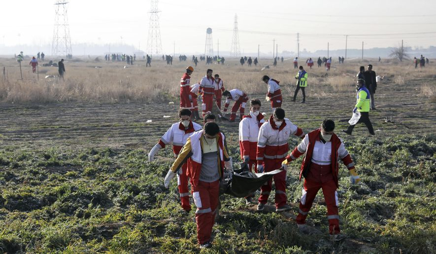 Rescue workers recover the bodies of victims of a Ukrainian plane crash in Shahedshahr, southwest of the capital Tehran, Iran, Wednesday, Jan. 8, 2020. A Ukrainian airplane carrying over 170 people crashed on Wednesday shortly after takeoff from Tehran's main airport, killing all onboard. (AP Photo/Ebrahim Noroozi)