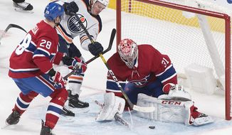 Edmonton Oilers' Joakim Nygard (10) moves in against Montreal Canadiens goaltender Carey Price as Canadiens' Marco Scandella defends during third-period NHL hockey game action in Montreal, Thursday, Jan. 9, 2020. (Graham Hughes/The Canadian Press via AP)
