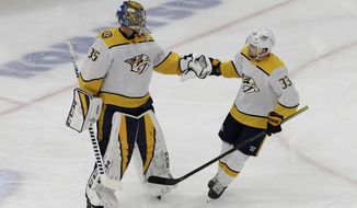 Nashville Predators right wing Viktor Arvidsson, right, celebrates with goalie Pekka Rinne after scoring a goal against the Chicago Blackhawks during the first period of an NHL hockey game in Chicago, Thursday, Jan. 9, 2020. (AP Photo/Nam Y. Huh)