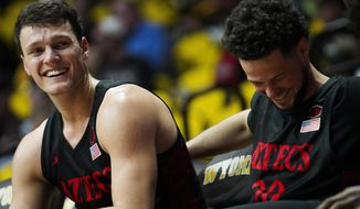 San Diego State forward Yanni Wetzell (5) and guard Jordan Schakel (20) laugh on the bench after a teammate accidentally stepped out of bounds while not under pressure during an NCAA college basketball game against Wyoming on Wednesday, Jan. 8, 2020, in Laramie, Wyo. (Nadav Soroker/Laramie Boomerang via AP)