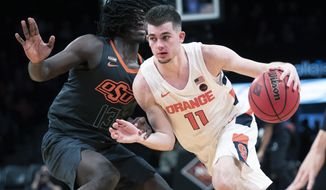 FILE - In this Wednesday, Nov. 27, 2019 file photo, Syracuse guard Joseph Girard III (11) drives against Oklahoma State guard Isaac Likekele (13) during the second half of an NCAA college semi final basketball game in the NIT Season Tip-Off tournament in New York. Freshman guard Joe Girard has become an important player for Syracuse as the Orange try to make some headway in the Atlantic Coast Conference. (AP Photo/Mary Altaffer, File)