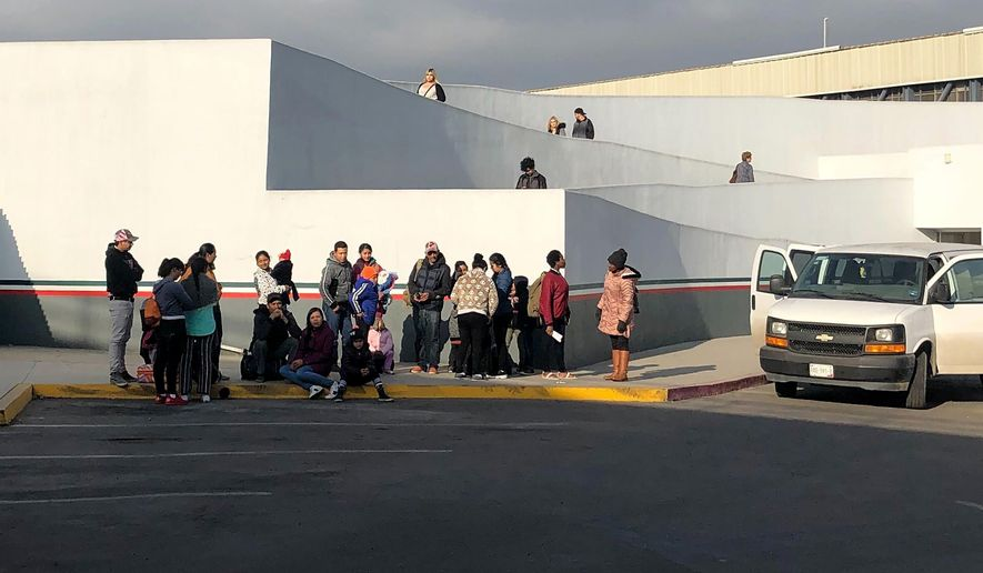 In this Wednesday, Jan. 8, 2020, photo people seeking asylum in the United States wait at the border crossing bridge in Tijuana, Mexico, just across the border from San Diego. The number of people arrested or stopped entering the U.S. along the Mexico border fell for a seventh straight month in December, with Mexicans making up a larger than usual part of the mix, authorities said Thursday. (AP Photo/Elliot Spagat)
