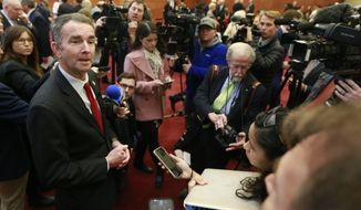 Virginia Gov. Ralph Northam, left, speaks to the medial after a news conference at the Virginia State Capitol in Richmond, Va., Thursday, Jan. 9, 2020. (AP Photo/Steve Helber)