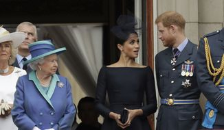 In this Tuesday, July 10, 2018, file photo Britain's Queen Elizabeth II, Meghan the Duchess of Sussex and Prince Harry stand on a balcony to watch a flypast of Royal Air Force aircraft pass over Buckingham Palace in London.  (AP Photo/Matt Dunham, File)