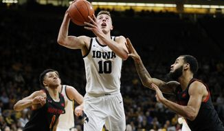 Iowa guard Joe Wieskamp (10) drives to the basket between Maryland's Anthony Cowan Jr., left, and Eric Ayala, right, during the second half of an NCAA college basketball game, Friday, Jan. 10, 2020, in Iowa City, Iowa. (AP Photo/Charlie Neibergall) ** FILE **