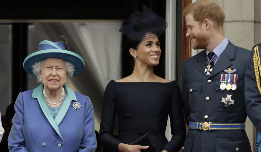In this Tuesday, July 10, 2018, file photo Britain's Queen Elizabeth II, and Meghan the Duchess of Sussex and Prince Harry watch a flypast of Royal Air Force aircraft pass over Buckingham Palace in London. (AP Photo/Matt Dunham, File)