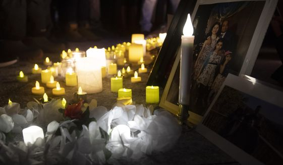 Candles sit in front of pictures of victims at a candle light vigil to remember those killed in the Ukraine International Airlines plane crash, Thursday, Jan. 9, 2020, in Ottawa, Ontario. The civilian Ukrainian jetliner crashed near Tehran late Tuesday, killing all 176 people on board. (Adrian Wyld/The Canadian Press via AP)