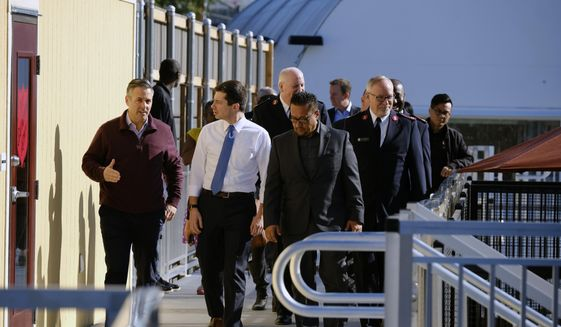 Democratic presidential candidate and former South Bend, Ind., Mayor Pete Buttigieg, center, is joined by City Councilmember Joe Buscaino, left, and Project Director Santiago Reyes while on a tour at A Bridge Home Project homeless shelter in Los Angeles on Friday, Jan. 10, 2020. (AP Photo/Richard Vogel)